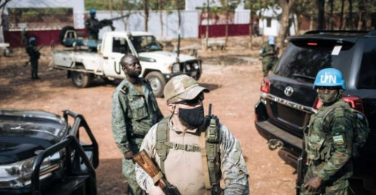 The United Nations Security Council has asked all forces in the Central African Republic to guarantee the safety of UN peacekeepers -- one is seen at right in 2020 in the capital Bangui.  By ALEXIS HUGUET (AFP/File)