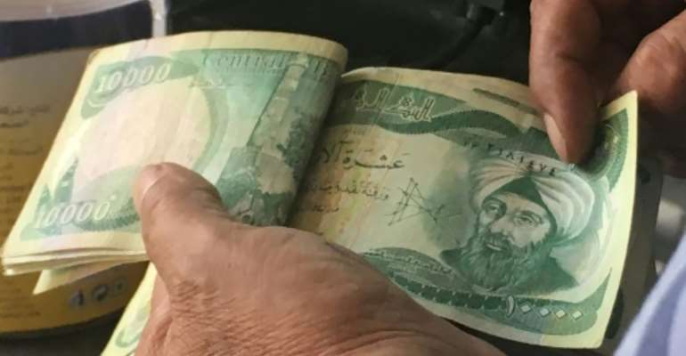 The United States is sanctioning seven financiers who allegedly helped funnel money to the Islamic State group -- seen here are 10,000-dinar banknotes in Iraq.  By Ali CHOUKEIR (AFP/File)