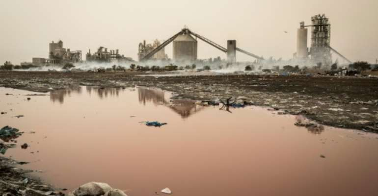 The view from Bargny: The small Senegalese village is caught between a cement victory, artisanal fish smokers and the plastic-strewn tide of the Atlantic.  By JOHN WESSELS (AFP)