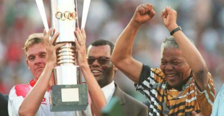 Then South Africa president Nelson Mandela (R) celebrates as captain Neil Tovey (L) holds the Africa Cup of Nations trophy after defeating Tunisia in the 1996 final.  By Mykel NICOLAOU (AFP/File)