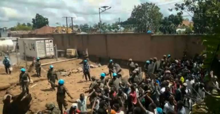 This frame grab taken from video footage shows crowds as they confront United Nations (UN) peackeepers in a UN compound on the outskirts of the eastern DRCongo town of Beni on November 25, 2019: protesters accused the UN troops of failing to protect them from armed militias who have killed hundreds.  By Ushindi Mwendapeke Eliezaire (AFP)