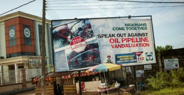 This photo taken on June 10, 2016 shows an advertising board concerning the oil pipeline vandalization in the City of Warri in Delta State.  By Stefan Heunis (AFP/File)