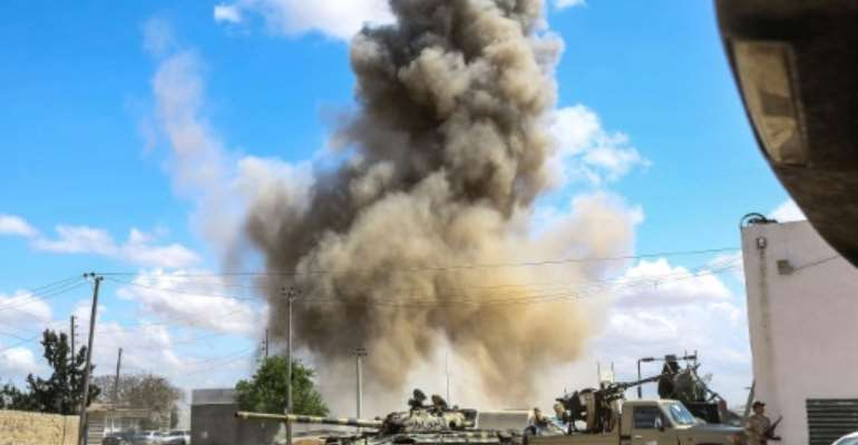 This picture taken on April 12, 2019 shows a smoke plume from an air strike behind a tank and technicals (pickup trucks mounted with turrets) of forces loyal to Libya's Government of National Accord (GNA), during clashes outside Tripoli. The UN wants the
