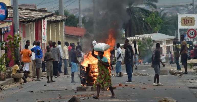 A woman walks past a burning barricade in the Kinanira neighborhood of Burundi's capital Bujumbura on May 21, 2015.  By Carl De Souza (AFP)