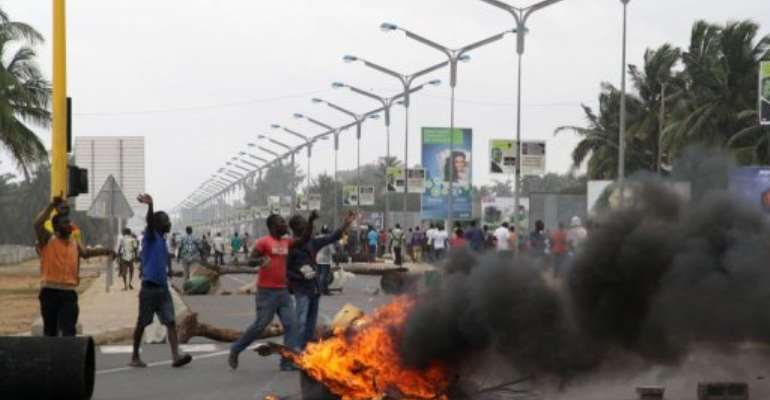 Opposition supporters burn tyres and demonstrate in Lome on August 22.  By Emile Kouton (AFP/File)