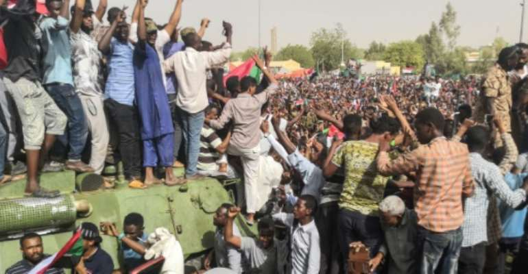 Thousands of jubilant Sudanese protesters fete troops posted outside army headquarters as top brass promise an