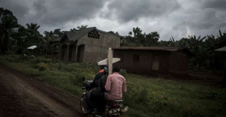 Toll: Three people on a motorbike carry a cross for a grave in Ebola-hit North Kivu.  By John WESSELS (AFP)