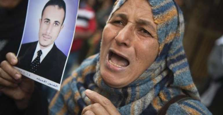 An Egyptian woman holding the portrait of a relative reacts outisde the court that sentenced 682 alleged Islamists and a Muslim Brotherhood leader to death on April 28, 2014 in the southern city of Minya.  By Khaled Desouki (AFP)