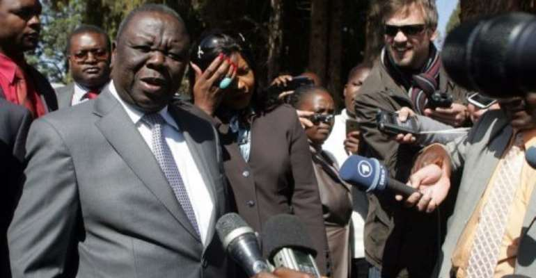 Zimbabwe's Prime Minister Morgan Tsvangirai (L) speaks to journalists after casting his ballot in Harare July 31, 2013.  By Jekesai Njikizana (AFP)