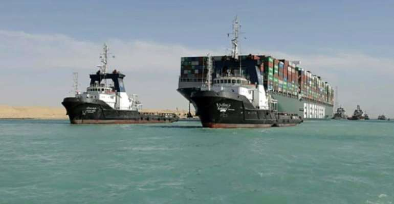 Tugboats guide the giant container vessel MV Ever Given through the Suez Canal after it was finally refloated, ending a near week-long closure of the vital trade artery.  By - (SUEZ CANAL AUTHORITY/AFP)