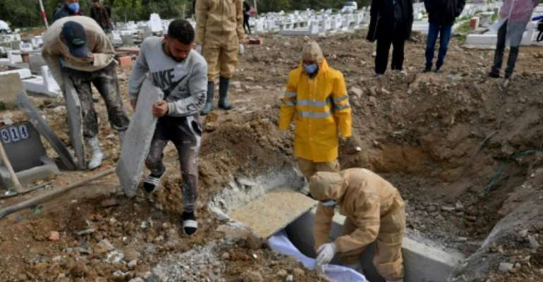 Tunis municipality employees bury the body of a Covid-19 victim at the Jellaz cemetery in the capital Tunis.  By FETHI BELAID (AFP)