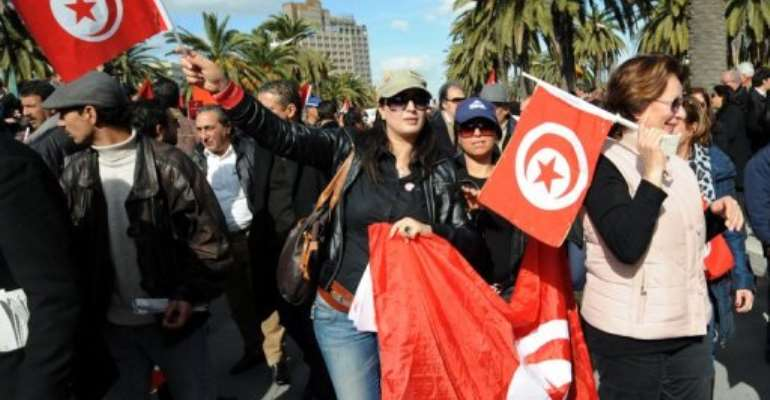 Tunisian people shout slogans and wave Tunisian flags during a demonstration on Habib Bourguiba Avenue in Tunis.  By Fethi Belaid (AFP/File)