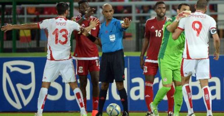 Referee Rajindraparsad Seechurn (C) tries to stop an argument during the 2015 African Cup of Nations quarter-final football match between Equatorial Guinea and Tunisia in Bata on January 31, 2015.  By Khaled Desouki (AFP/File)