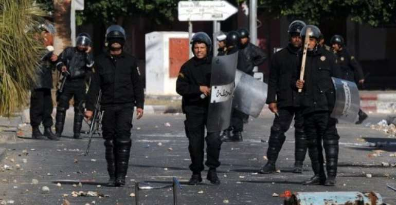 Tunisian riot police stand on a street covered by debris after clashing with demonstrators near Sidi Bouzid.  By Str (AFP/File)