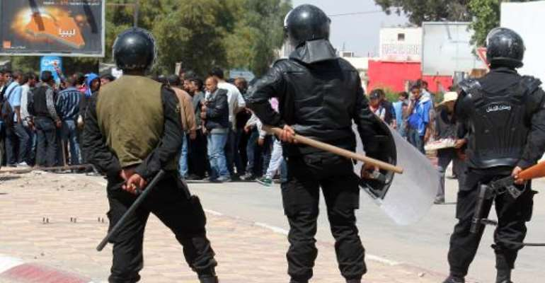 Tunisian riot police face residents of the southeastern town of Ben Guerdane during a general strike on April 2, 2014.  By Jawad Nasri (AFP/File)