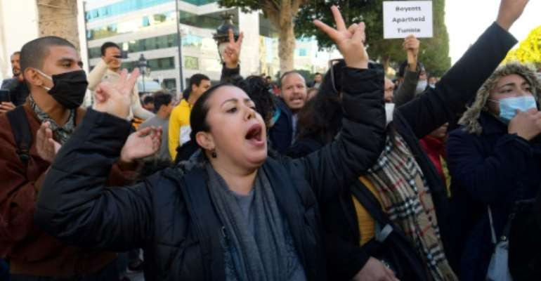 Tunisian  protesters shout slogans during an anti-government demonstration on Habib Bourguiba Avenue in the capital Tunis, on January 20, 2021  Young Tunisians clashed with security forces overnight and protest organisers called for anti-government rallies after five days of riots in disadvantaged neighbourhoods..  By FETHI BELAID (AFP)