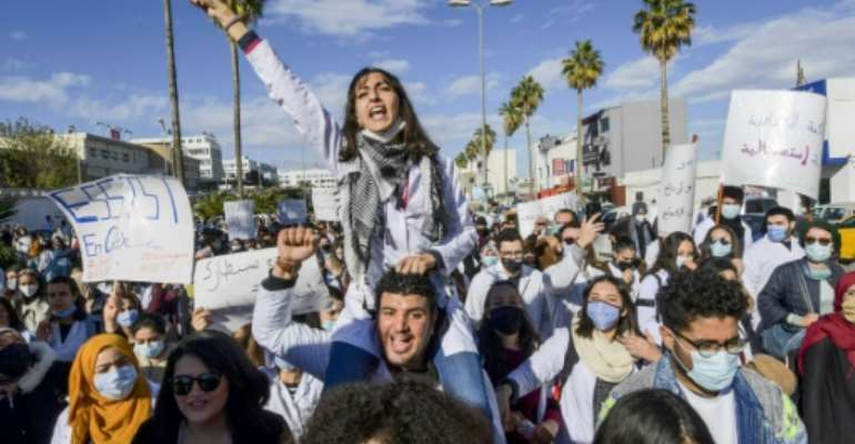Tunisian doctors demonstrate in the capital Tunis over the country's crumbling public health infrastructure, following the death of a young doctor in a lift accident.  By FETHI BELAID (AFP)