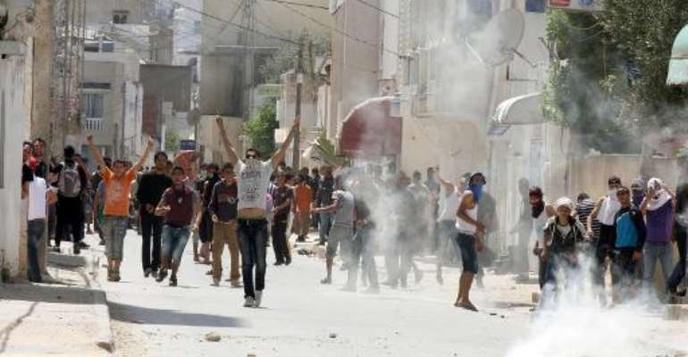 Tunisian police fire tear gas during clashes with radical Islamists on May 19, 2013 in a neighbourhood west of Tunis, after Salafist movement Ansar al-Sharia told its followers to gather.  By Khalil (AFP/File)