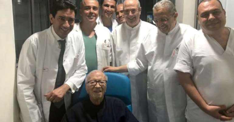 Tunisian President Beji Caid Essebsi smiles as he leaves hospital surrounded by his doctors.  By - (Tunisian Presidency/AFP)