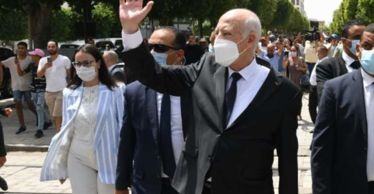 Tunisian President Kais Saied, who has suspended parliament, waves as he walks with security guards in central Tunis on August 1, 2021.  By - (TUNISIAN PRESIDENCY/AFP/File)
