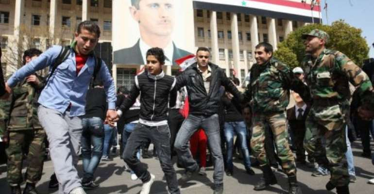 Syrian soldiers dance with government supporters in front of a portrait of Syrian President Bashar Al-Assad.  By Louai Beshara (AFP)