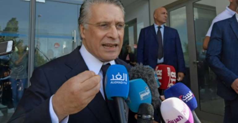 Tunisian presidential candidate Nabil Karoui speaks to journalists after being freed from jail where he was detained for over a month in connection with a money laundering probe ahead of Sunday's election runoff.  By FETHI BELAID (AFP)