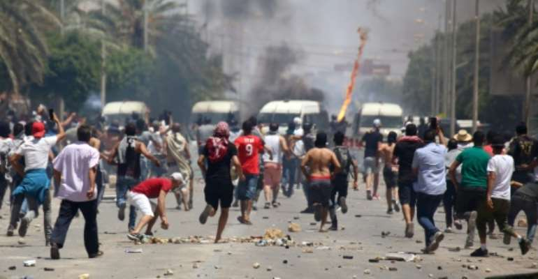Tunisian protesters clash with security forces as they demonstrate in the southern city of Tataouine demanding authorities make good on a 2017 promise to provide jobs in the gas and oil sector.  By FATHI NASRI (AFP)