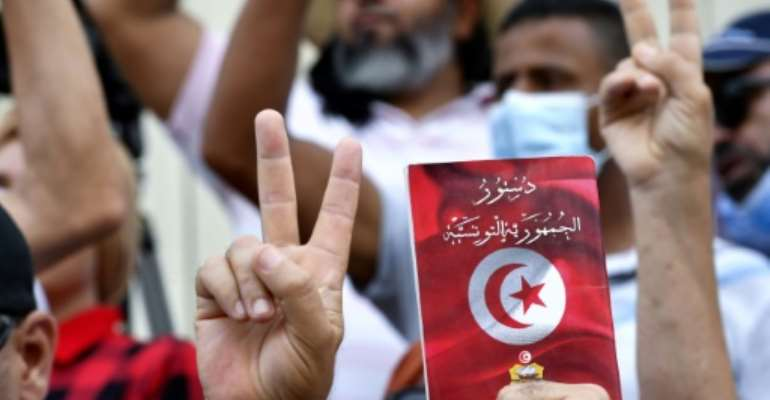 Tunisian protesters wave copies of the constitution as they march through the capital to demand an end to the sweeping extraordinary powers assumed by President Kais Saied in July.  By FETHI BELAID (AFP)