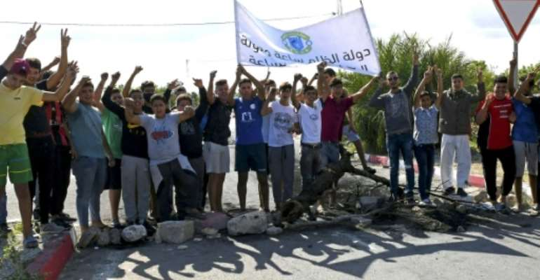 Tunisian youths prepare to burn tires and block the road leading to the city of Chebba on October 19 in protest at the Tunisian Football Federation's decision to ban their local club CS Chebba.  By Bechir TAIEB (AFP)