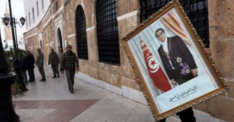 An employee at the prime minister's office removes a portrait of president Ben Ali last January after he fled into exile.  By Fethi Belaid (AFP/File)