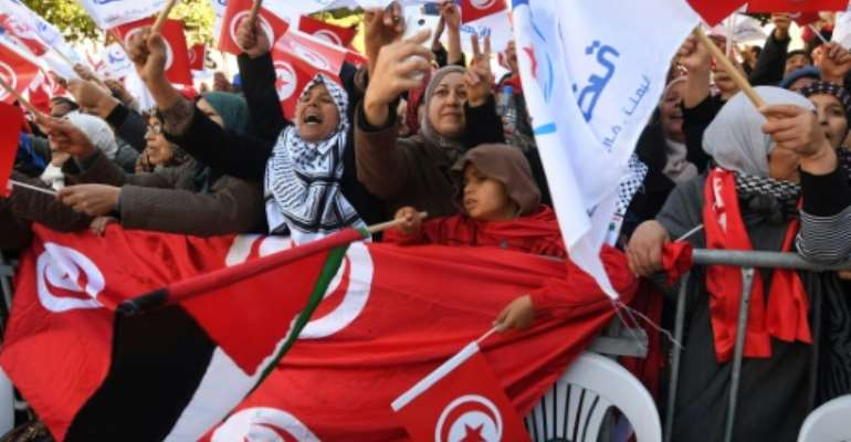 Tunisians wave their national flag and the flag of the Ennahda Islamist party as they gather on Habib Bourguiba Avenue in Tunis on January 14, 2018 to mark the seventh anniversary of the uprising that launched the Arab Spring.  By FETHI BELAID (AFP)