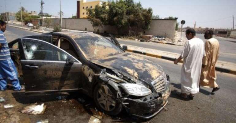 Libyans walks past the destroyed bullet proof car of Libyan former Prime Minister Baghdadi al-Mahmoudi in Tripoli.  By Patrick Baz (AFP/File)