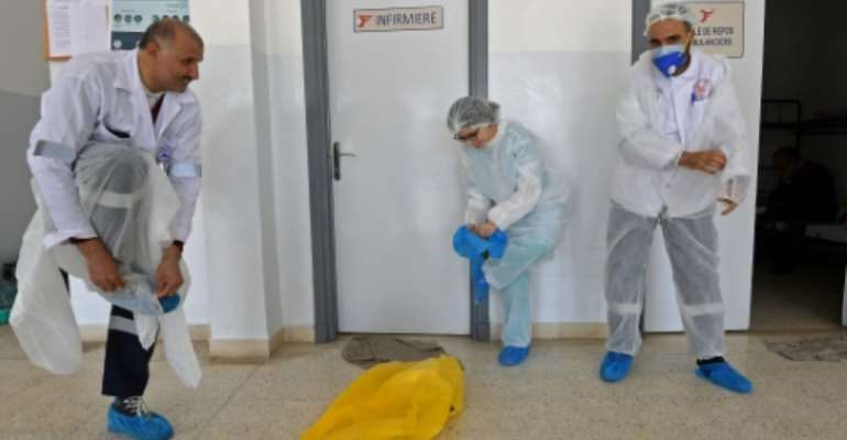 Tunisia's emergency medical care doctors (pictured April 6, 2020) dress in personal protective equipment as a measure of protection against the coronvirus, before heading out to treat a COVID-19 patient in the capital Tunis.  By FETHI BELAID (AFP/File)