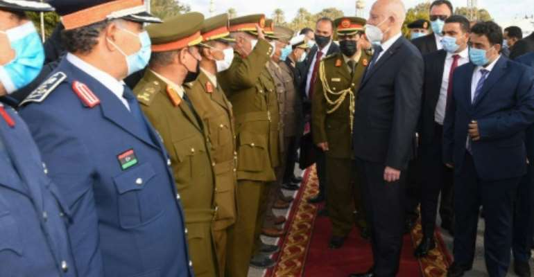 Tunisia's President Kais Saied (C) was received by Libya's new Head of the Presidential Council, Mohammad Menfi (R), and military officials.  By STRINGER (Tunisian presidency Facebook page/AFP)