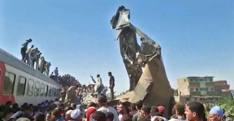 Twisted metal juts from the wreckage of a train collision that killed at least 32 people and injured more than 160 in southern Egypt.  By - (AFP)
