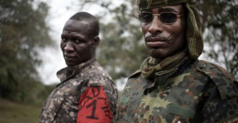 Two brigade leaders from the UPC armed group pose for photographs in the city of Bokolobo, near Bambari on March 16, 2019.  By FLORENT VERGNES (AFP/File)