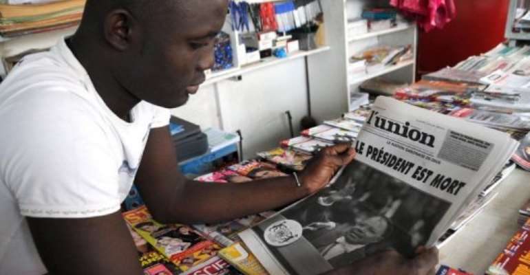 A young man reads a newspaper in Gabon.  By Wils Yanick Maniengui (AFP/File)