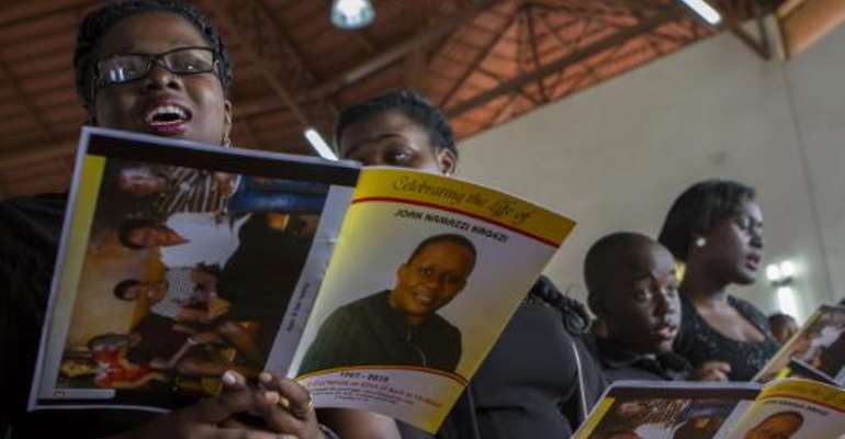 Children of the late acting assistant director of public prosecution Joan Kagezi attend a church service for their mother on April 2, 2015 in Kampala.  By Isaac Kasamani (AFP)