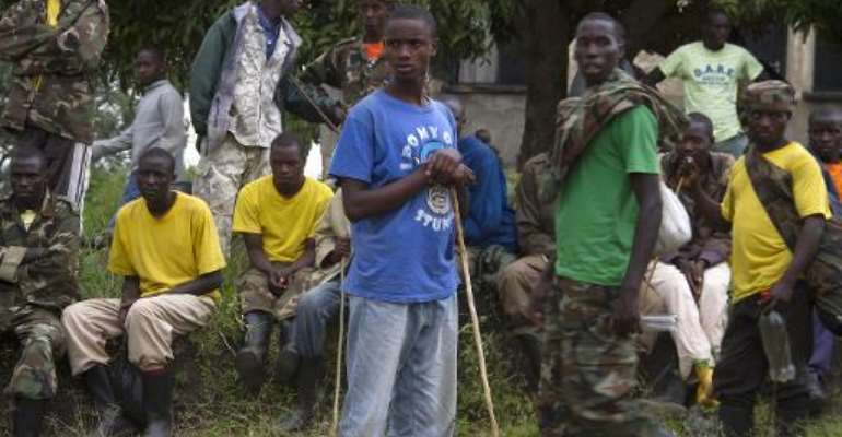 Members of the Democratic Republic of Congo rebel group M23 stand at the Ramwanja refugee settlement on December 17, 2014.  By Isaac Kasamani (AFP/File)