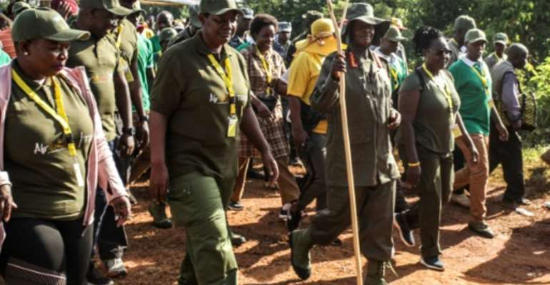 Ugandan President Yoweri Museveni and veterans and Members of Parliament, march through the jungle as he retraces the route which his guerrilla forces took 35 years ago.  By Hajarah Nalwadda (AFP)