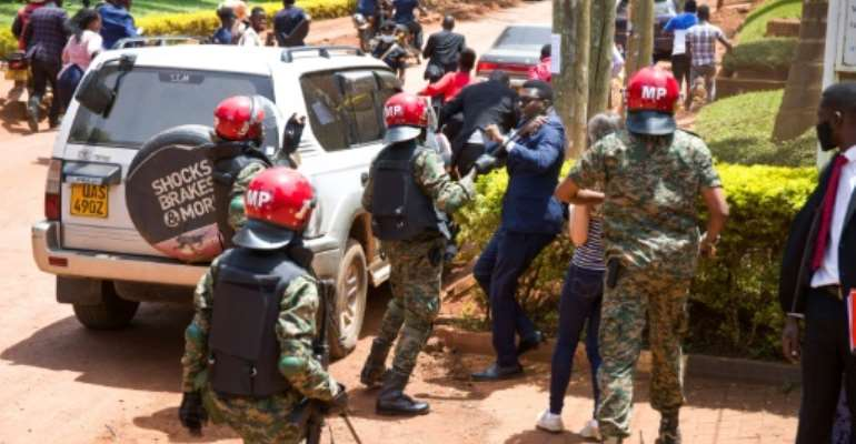 Ugandan security forces beat journalists covering Bobi Wine filing a petition with the UN against human rights abuses.  By Badru KATUMBA (AFP)