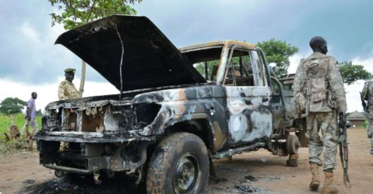 South Sudanese SPLA soldiers inspect a burned out car in Pageri on August 20, 2015.  By Samir Bol (AFP/File)