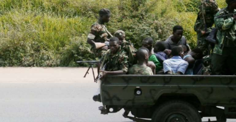 A military vehicle, carrying men tied up, drives through the Musaga neighbourhood of the city of Bujumbura on December 11, 2015.  By  (AFP/File)