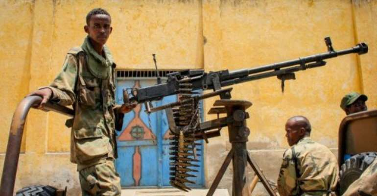 A fighter of the pro-government Ras Kimboni Brigade arms a heavy machine gun in Kismayo, on October 7, 2012.  By Stuart Price (AU-UN IST/AFP)