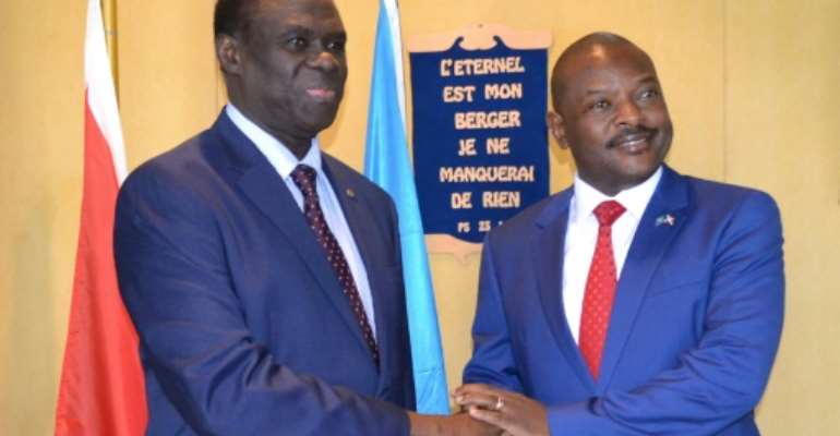 UN envoy to Burundi Michel Kafondo (L) shakes hands with Burundi's President Pierre Nkurunziza ahead of a meeting in June 2017.  By STR (AFP/File)