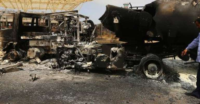 The wreckage of a truck and an airplane are seen at Tripoli international airport in the Libyan capital on July 14, 2014.  By Mahmud Turkia (AFP)