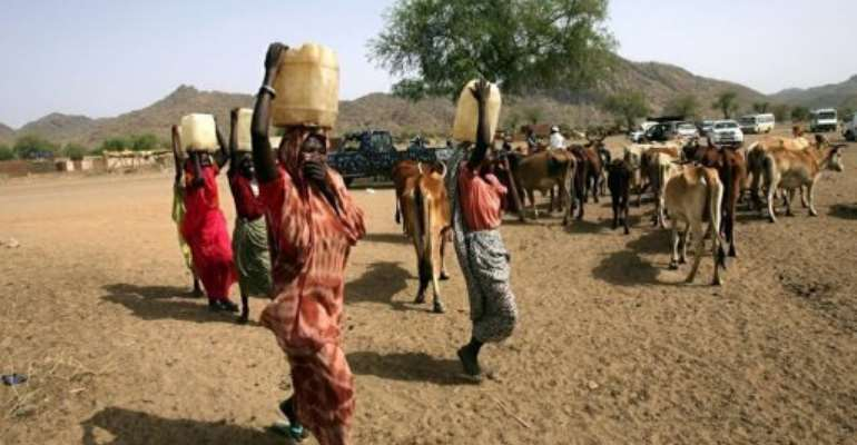 Sudanese women carry water in the town of Kadugli in the northern state of South Kordofan in 2011.  By Ashraf Shazly (AFP/File)