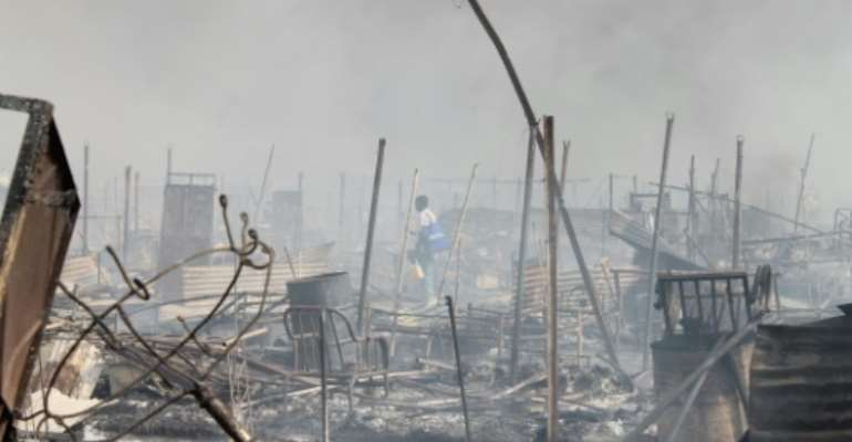People walk among rubble in an United Nations base in the northeastern town of Malakal on February 18, 2016.  By Justin Lynch (AFP/File)