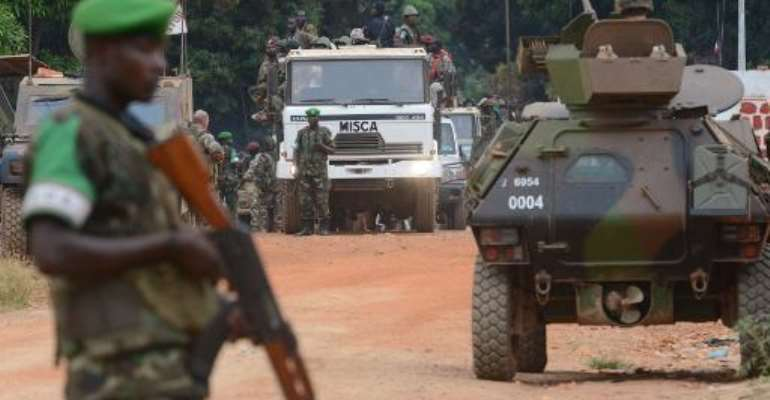 Former Seleka militants are escorted by French troops of the Sangaris operation and Rwanda's MISCA peacekeepers out of Kassai military camp in Bangui on their way to another camp outside the city on January 28, 2014.  By Issouf Sanogo (AFP)