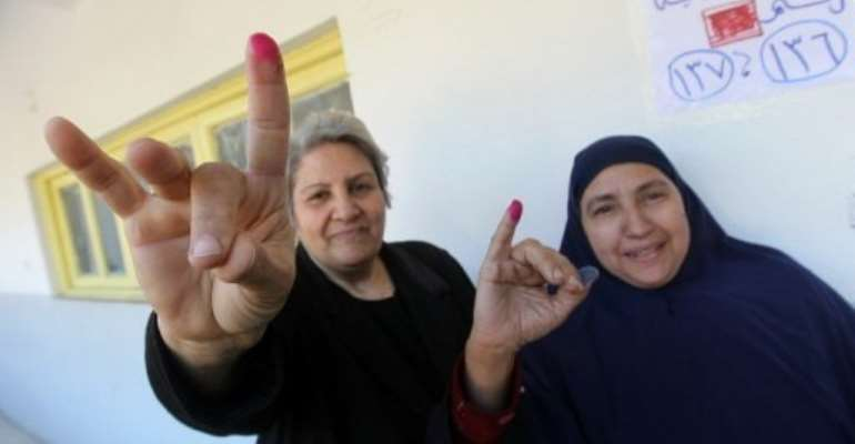 Egyptian women show their ink-stained fingers after voting at a polling station in Cairo's al-Sahel district yesterday.  By Khaled Desouki (AFP)